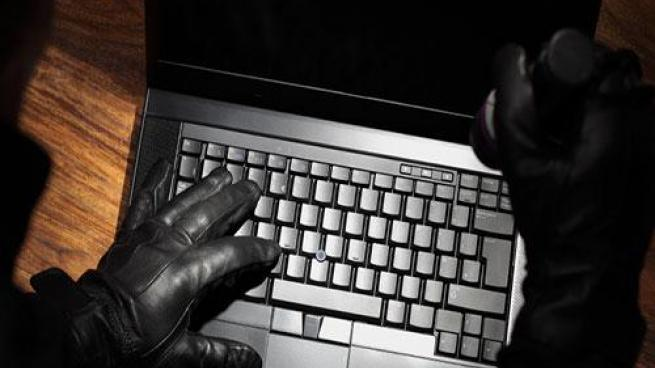 Gloved hands typing on keyboard