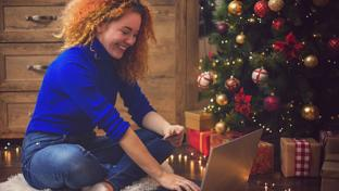 Woman shopping online in front of Christmas tree