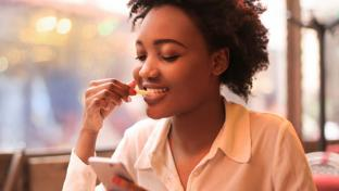 woman checking phone while eating fries