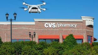 Drone holding UPS package flying over CVS