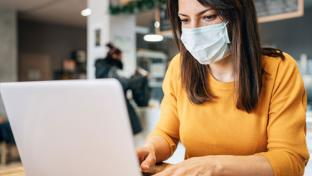 woman on laptop wearing mask