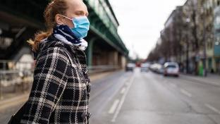 Woman crossing street with mask